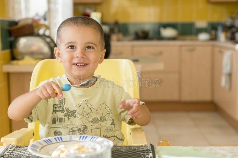 Szczęśliwa chłopiec łasowania owsianka Chłopiec łasowania śniadanie przy stołem zdjęcia stock
