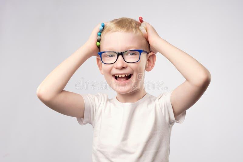 Szczęśliwa chłopiec śmia się mienie markierów w rękach zdjęcia stock