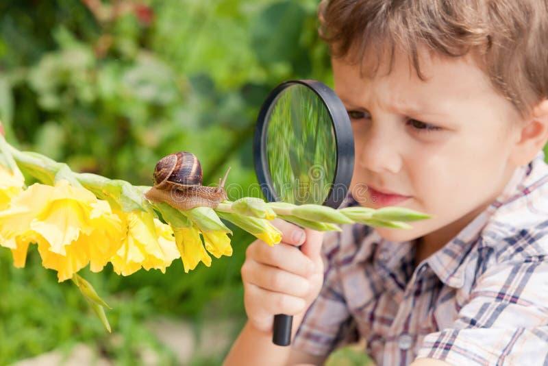 Szczęśliwa chłopiec bawić się w parku z ślimaczkiem przy dnia czasem zdjęcia stock