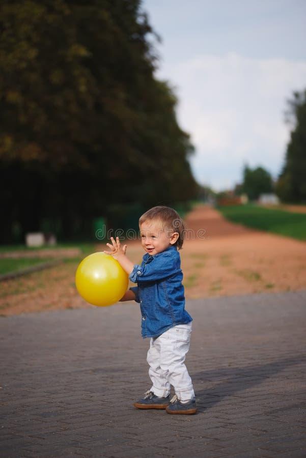 Szczęśliwa chłopiec bawić się z żółtą piłką zdjęcia stock