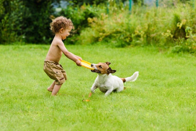 Szczęśliwa chłopiec bawić się z psią aktywną grze na gazonie fotografia royalty free