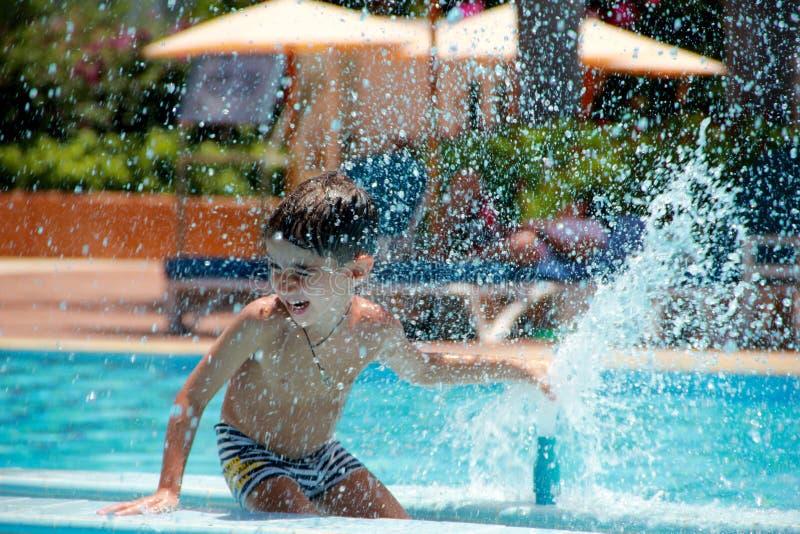 Szczęśliwa chłopiec bawić się z wodną fontanną w basenie zdjęcia royalty free