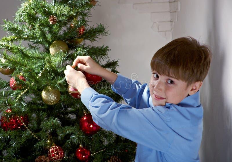 Szczęśliwa chłopiec dekoruje choinki ja zdjęcia stock