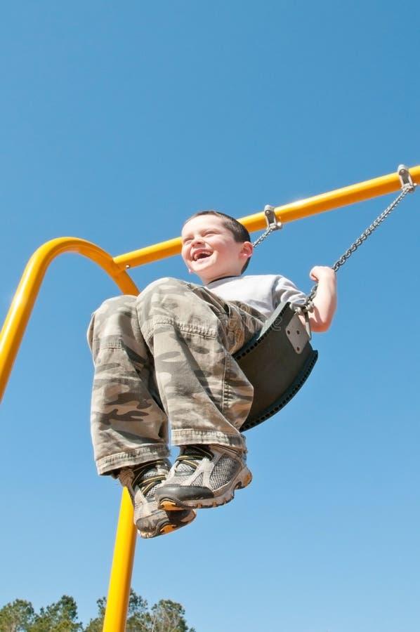 szczęśliwa chłopiec huśtawka obraz stock