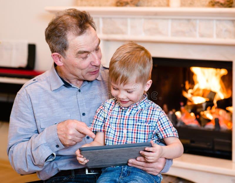 Szczęśliwa chłopiec i jego dziad używa pastylka komputer obrazy royalty free