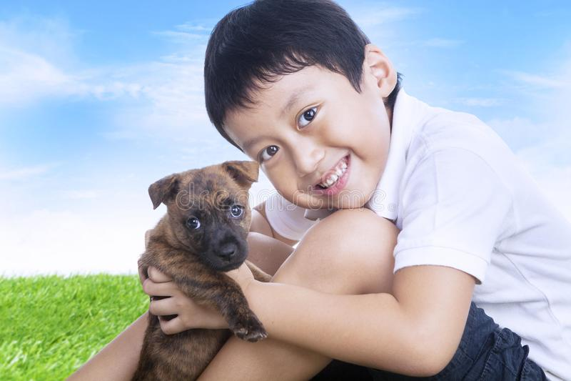 Download Szczęśliwa Chłopiec I Szczeniak Outdoors Zdjęcie Stock - Obraz złożonej z japończycy, wyrażenie: 28964294