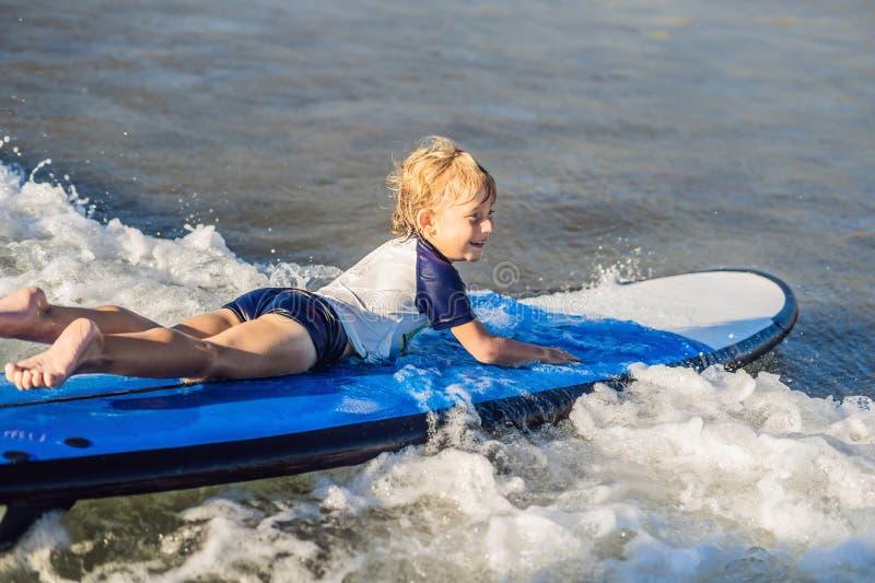 Szczęśliwa chłopiec - młoda surfingowiec przejażdżka na surfboard z zabawą na morzu zdjęcie royalty free