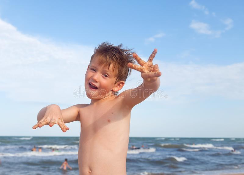 Szczęśliwa chłopiec ma zabawę na tle morze zdjęcie royalty free