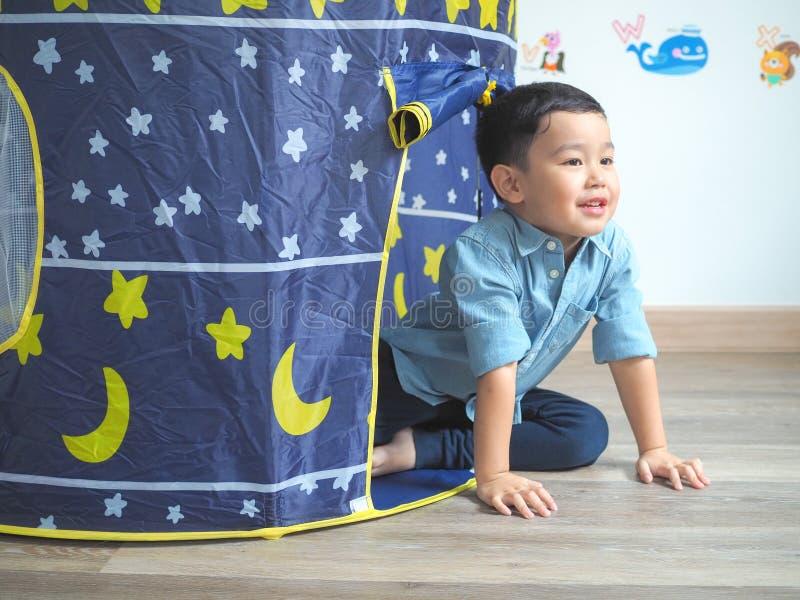 Szczęśliwa chłopiec ma zabawę z sztuka namiotem w domu fotografia stock
