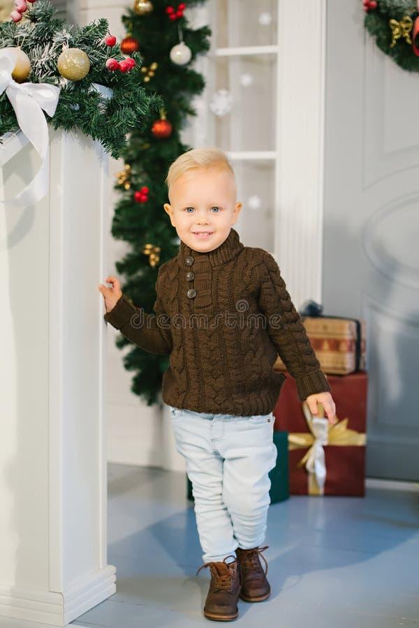 Szczęśliwa chłopiec na tle Bożenarodzeniowi prezenty zdjęcie royalty free