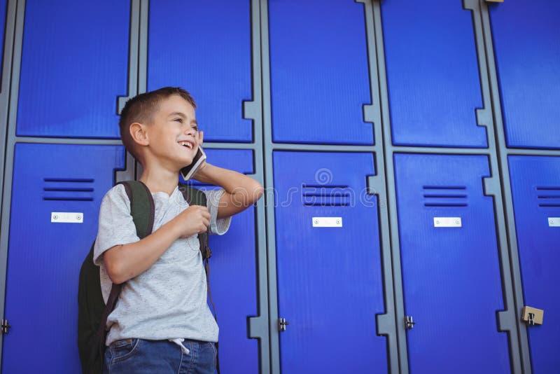 Szczęśliwa chłopiec opowiada na telefonie komórkowym przeciw szafkom obraz stock