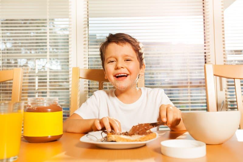Szczęśliwa chłopiec podesłania czekolada z nożem na grzance obrazy stock