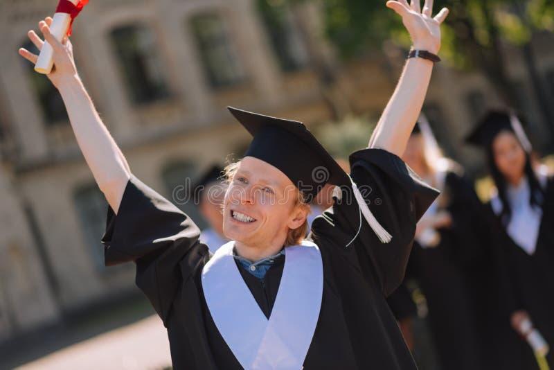 Szczęśliwa chłopiec podnosi jego ręki w powietrzu fotografia stock