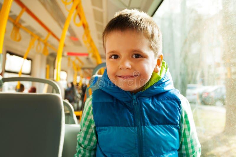 Szczęśliwa chłopiec podróżuje miasto transportem publicznym obraz royalty free