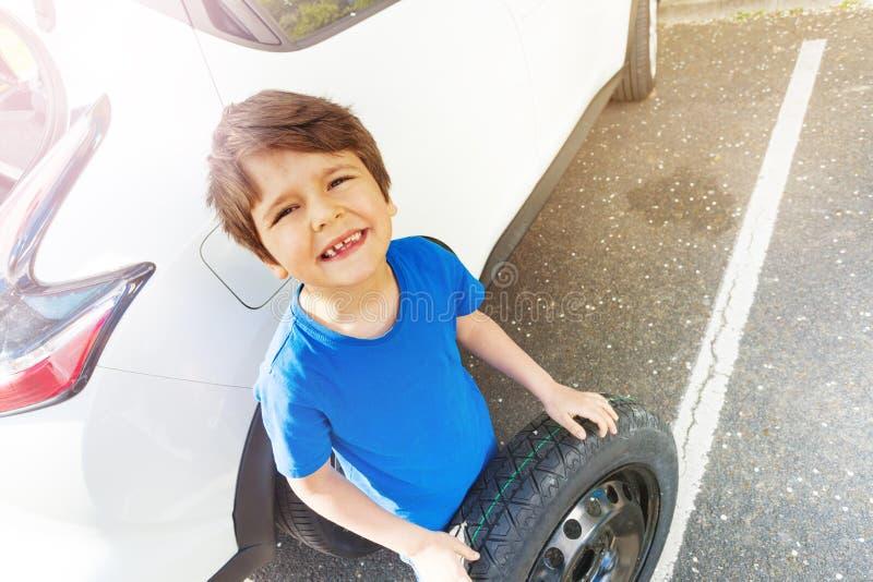Szczęśliwa chłopiec pozycja obok samochodu z dodatkową oponą obrazy stock
