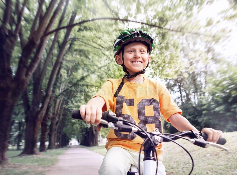 Szczęśliwa chłopiec przejażdżka bicykl w miasto parku zdjęcia stock