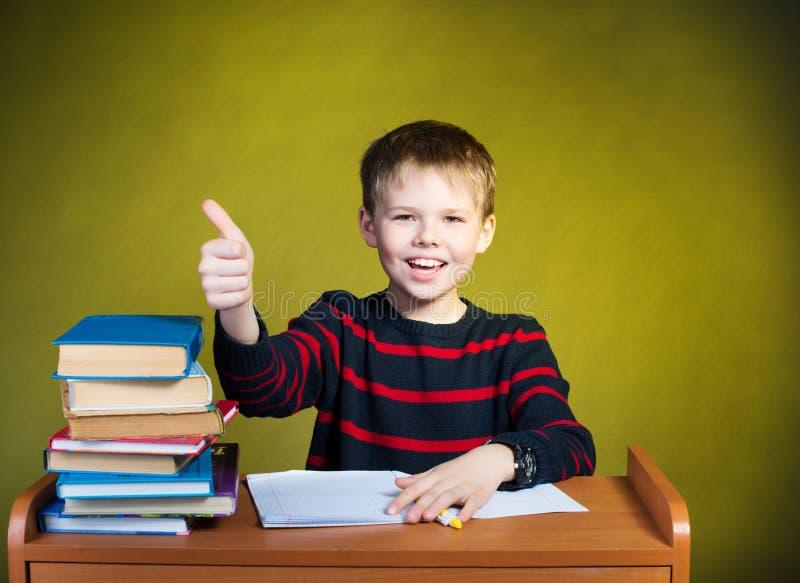Szczęśliwa chłopiec robi pracie domowej z kciukiem up, książki na t obrazy royalty free