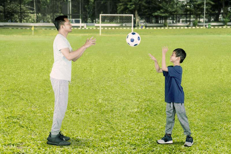 Szczęśliwa chłopiec rzuca piłkę jego ojciec obraz stock