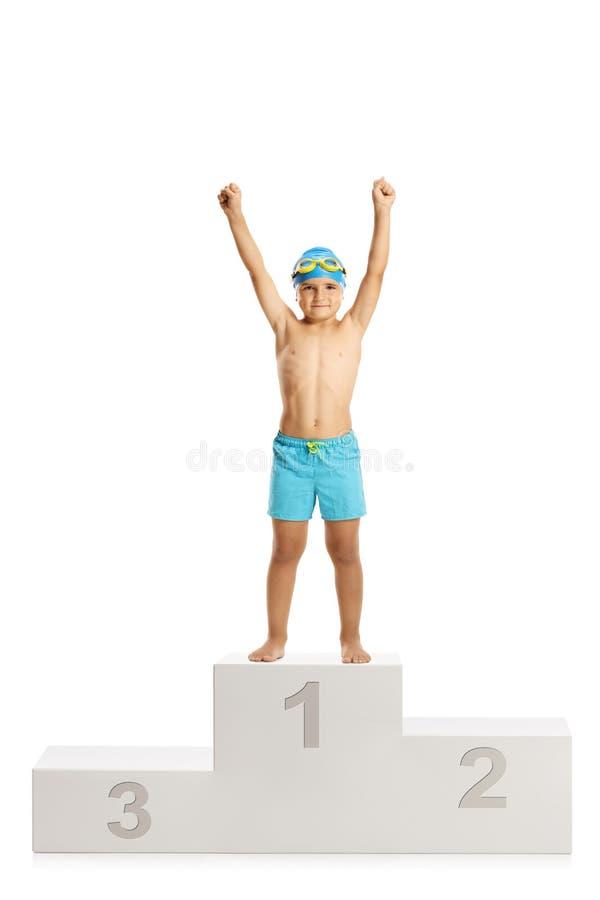 Szczęśliwa chłopiec stoi na zwycięzcy piedestału chwycie w pływackich bagażnikach obrazy stock
