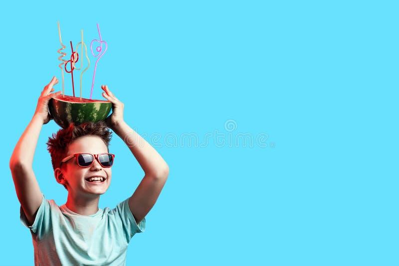 Szczęśliwa chłopiec trzyma arbuza z koktajlem w okularach przeciwsłonecznych ruruje na głowie na błękitnym tle obrazy stock