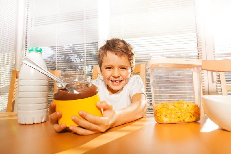 Szczęśliwa chłopiec trzyma szkło może z czekoladą rozprzestrzeniać obraz royalty free