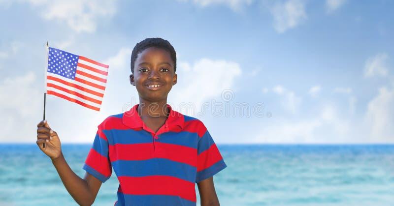 Szczęśliwa chłopiec trzyma usa flaga w plaży obrazy stock