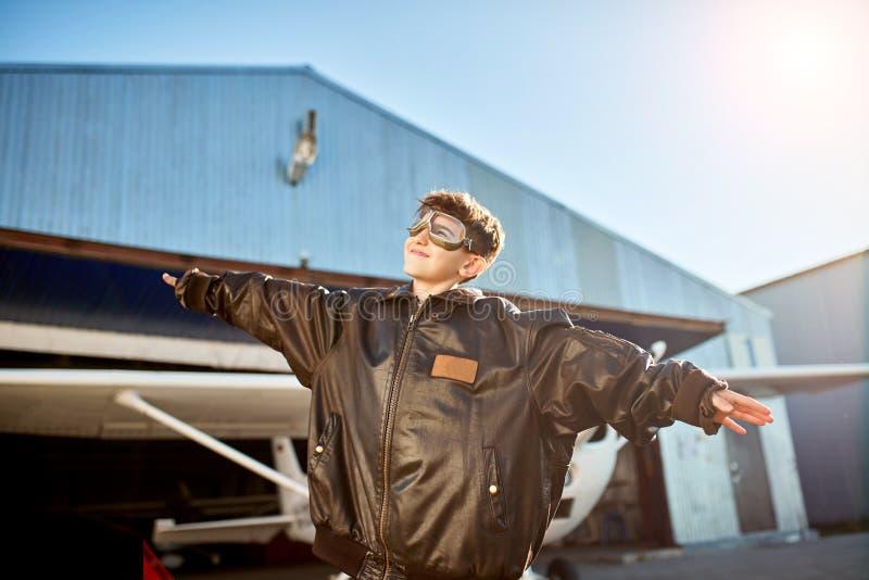 Szczęśliwa chłopiec w ampuła pilocie jest samolotowa, bawić się blisko hangaru kurtka udaje go zdjęcie royalty free