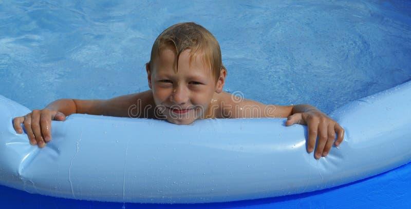 Szczęśliwa chłopiec z blondynem i niebieskimi oczami pływa w nadmuchiwanym basenie z jasną błękita jasnego wodą na pogodnym letni zdjęcia royalty free