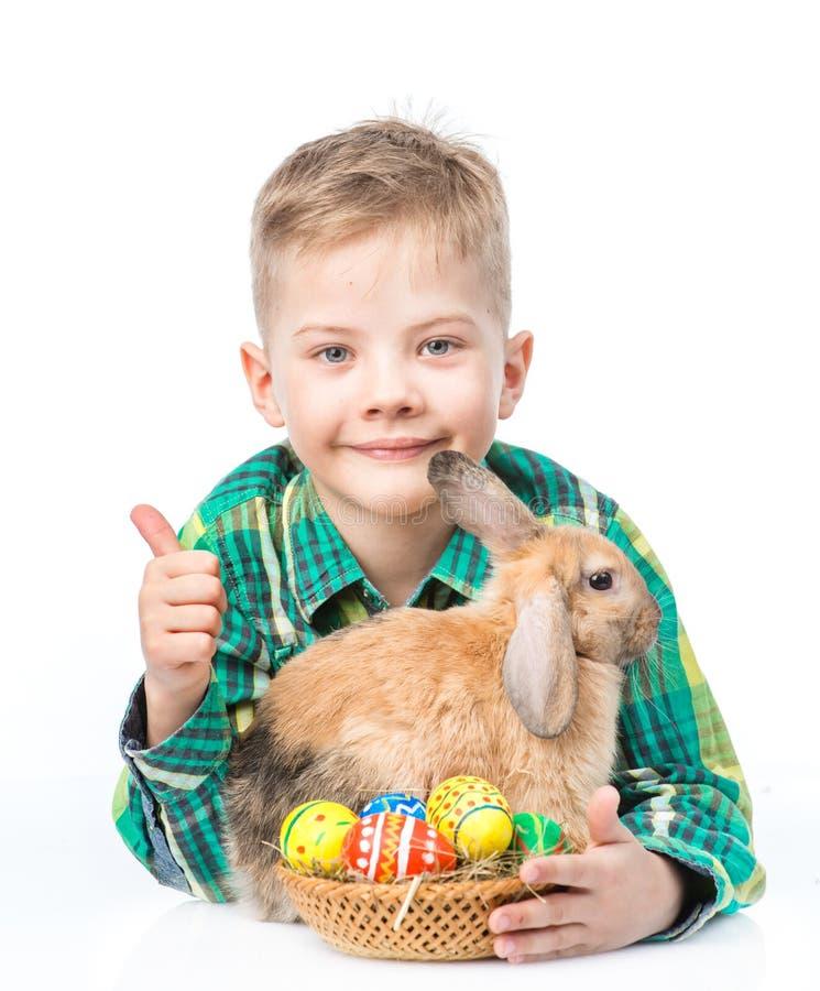 Szczęśliwa chłopiec z Easter jajkami obejmuje królika i pokazuje aprobaty pojedynczy białe tło zdjęcie royalty free