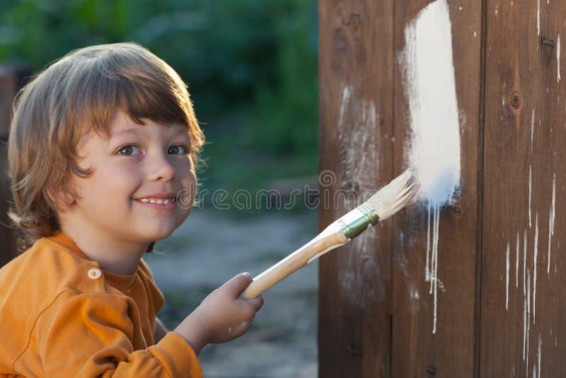 Szczęśliwa chłopiec z farby muśnięciem zdjęcia stock