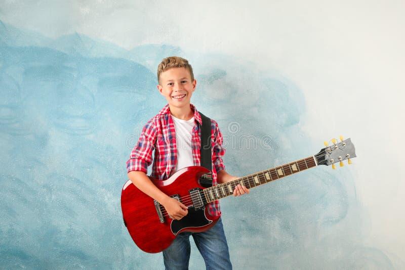 Szczęśliwa chłopiec z gitarą elektryczną na koloru tle obraz royalty free