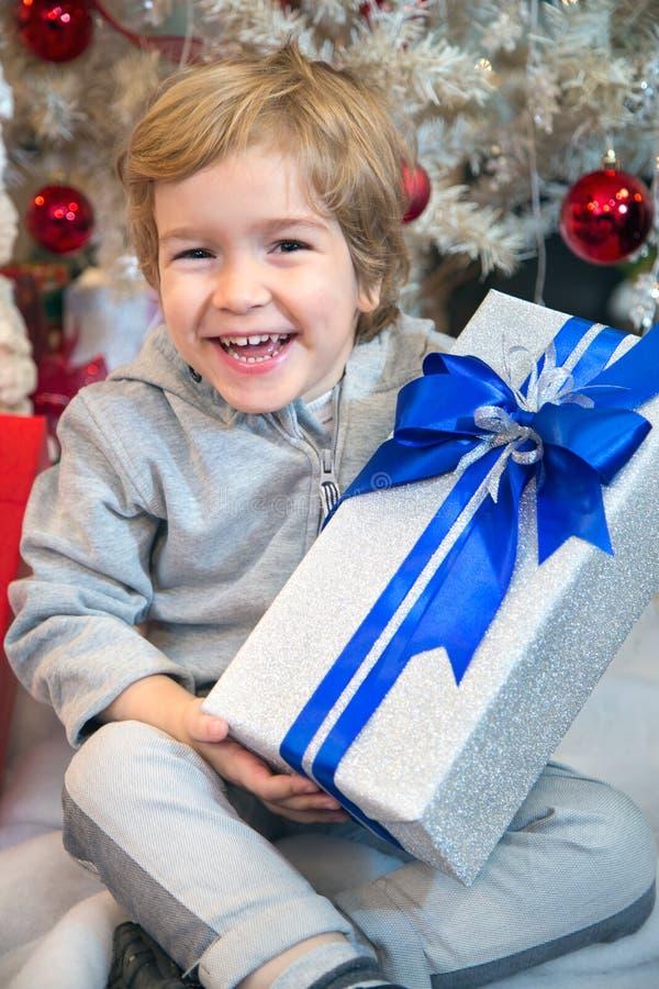 Szczęśliwa chłopiec z wakacyjnego prezenta pudełkiem obraz stock