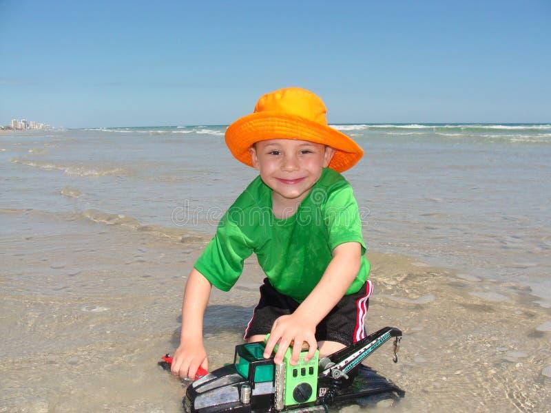 Szczęśliwa chłopiec z Zabawkarskim żurawiem na plaży zdjęcie royalty free