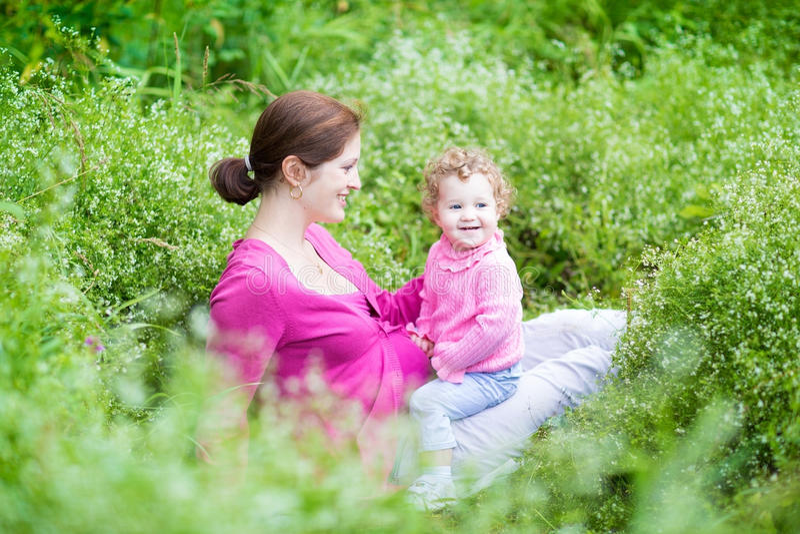 Szczęśliwa ciężarna matka bawić się z jej dziecko córką fotografia royalty free