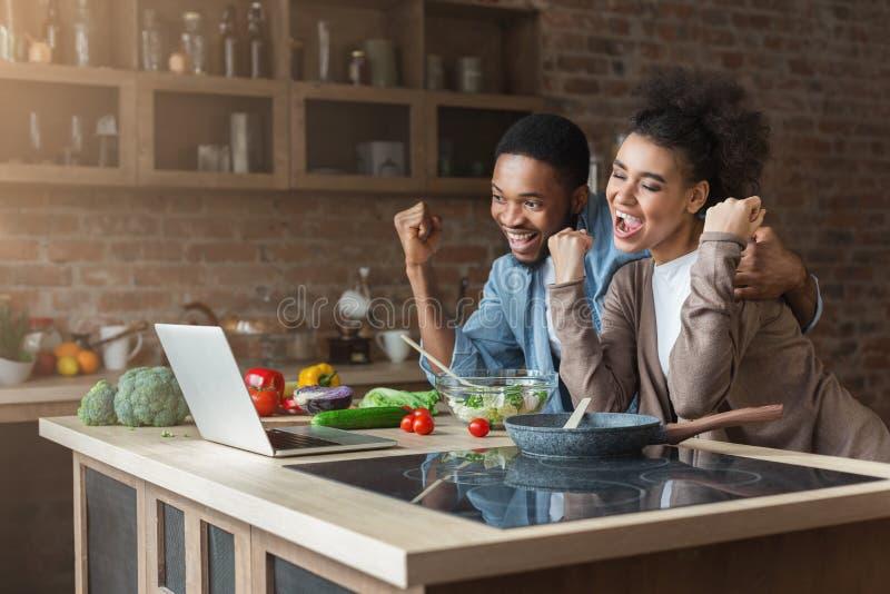 Szczęśliwa czarna para gotuje i patrzeje na laptopie z nastroszonymi rękami obraz royalty free