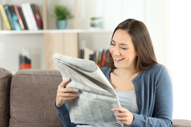 Szczęśliwa dama czyta gazetę w domu zdjęcie stock
