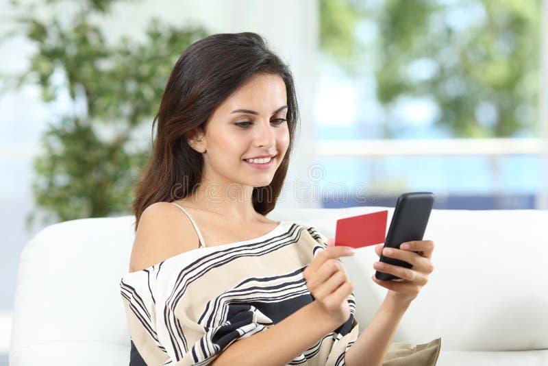 Szczęśliwa dama płaci online używać kartę kredytową w domu fotografia stock
