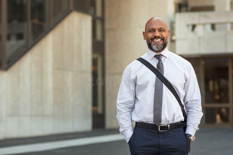 Szczęśliwa dojrzała biznesmen pozycja na ulicie fotografia royalty free