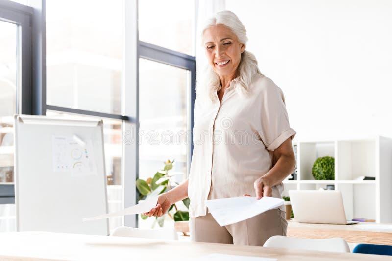 Szczęśliwa dojrzała biznesowa kobieta analizuje dokumenty zdjęcia royalty free
