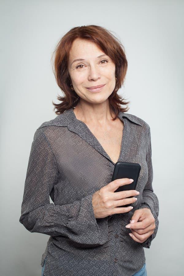 Szczęśliwa dojrzała biznesowa kobieta z telefonem komórkowym obrazy royalty free