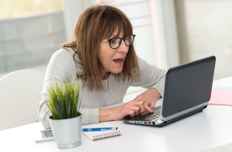 Szczęśliwa dojrzała kobieta ma dobrą niespodziankę na laptopie zdjęcia stock