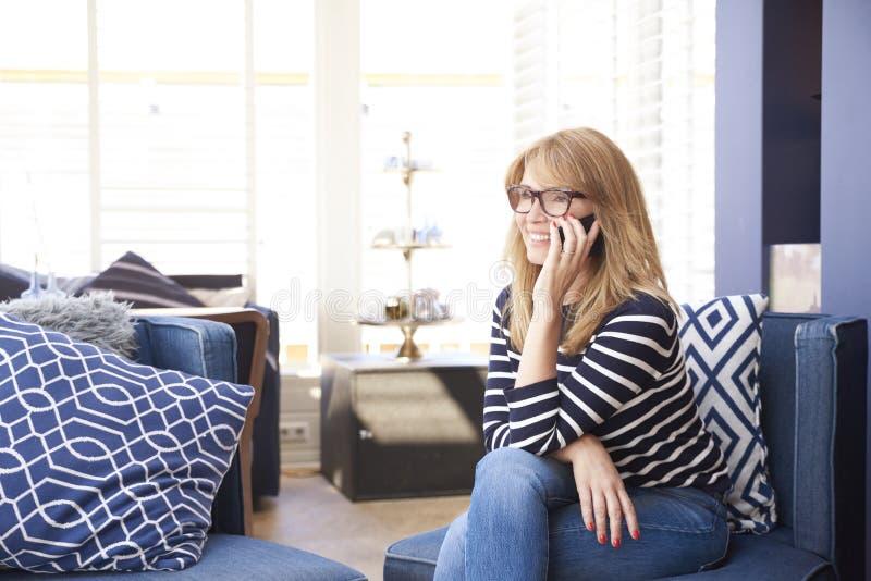 Szczęśliwa dojrzała kobieta opowiada z somebody na jej telefonie komórkowym podczas gdy siedzący na kanapie zdjęcia stock