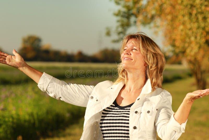 Szczęśliwa dojrzała kobieta otwarta ona ręki podczas gdy cieszący się sunbeams zdjęcia royalty free