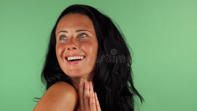 Szczęśliwa dojrzała kobieta patrzeje zaskakujący na zielonym chromakey obrazy royalty free