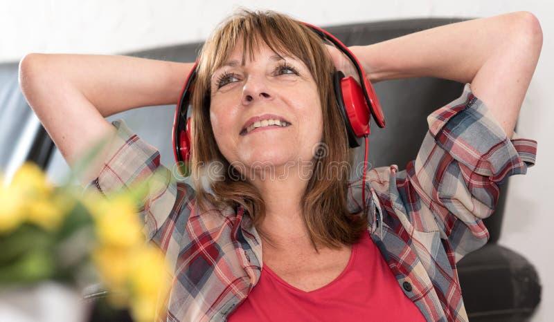 Szczęśliwa dojrzała kobieta słucha muzyka obrazy royalty free