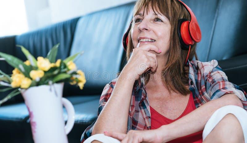 Szczęśliwa dojrzała kobieta słucha muzyka zdjęcie royalty free