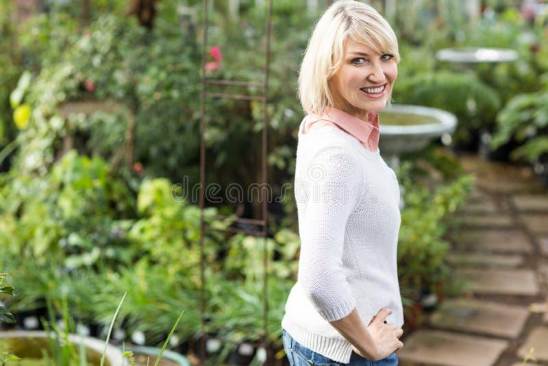 Szczęśliwa dojrzała kobieta z ręką na biodrze przy szklarnią zdjęcie stock
