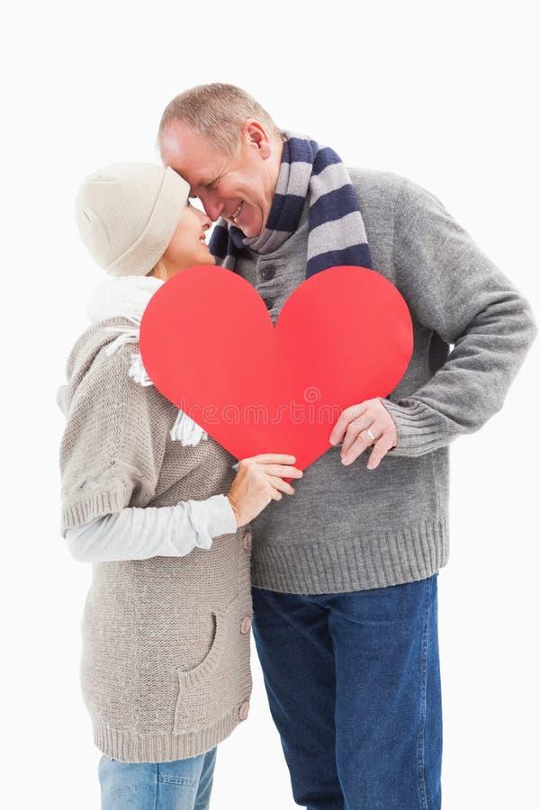 Szczęśliwa dojrzała para w zimy mienia czerwieni odzieżowym sercu obrazy stock