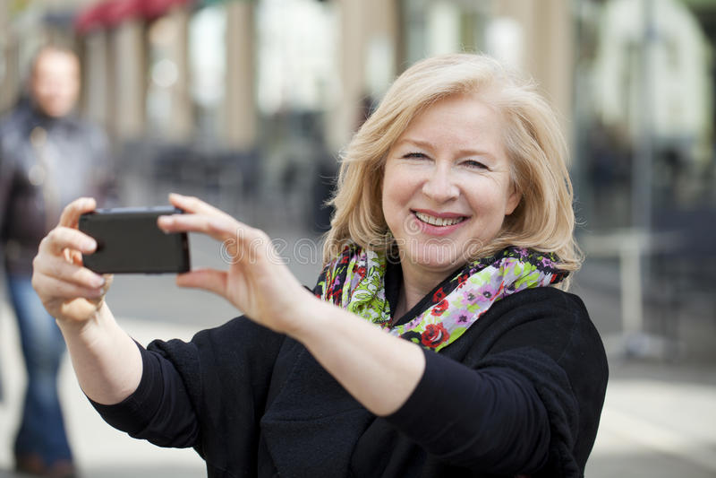 Szczęśliwa Dojrzała piękna blondynki kobieta fotografująca na telefonie komórkowym zdjęcia royalty free
