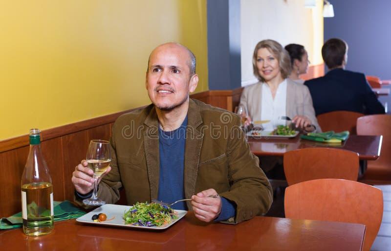 Szczęśliwa dojrzała samiec ma posiłek z winem obraz royalty free